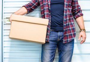 Man by storage unit with box