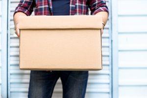 Mini Storage - Man holds file folder box.
