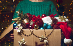 woman holds Christmas decorations